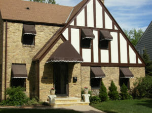 Window and hip style awnings with white scalloped stencil accentuate this lovely Minnesota home