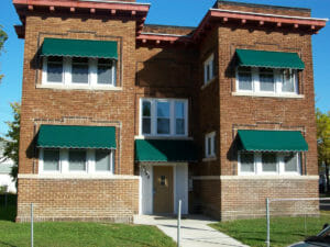 Twin Cities brick 4-plex accented with green window awnings